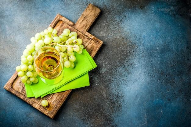 Copa de vino blanco con una rama de uvas, sobre una mesa blanca de mármol,