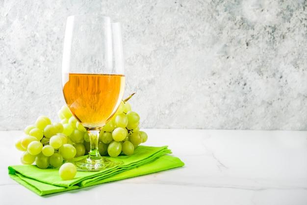 Copa de vino blanco con una rama de uvas