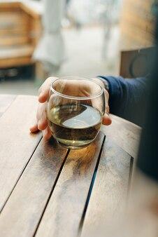 Copa de vino blanco sobre mesa de madera vintage en restaurante