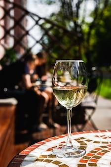 Una copa de vino blanco sobre una mesa de piedra de mosaico de una cafetería con terraza en un día soleado
