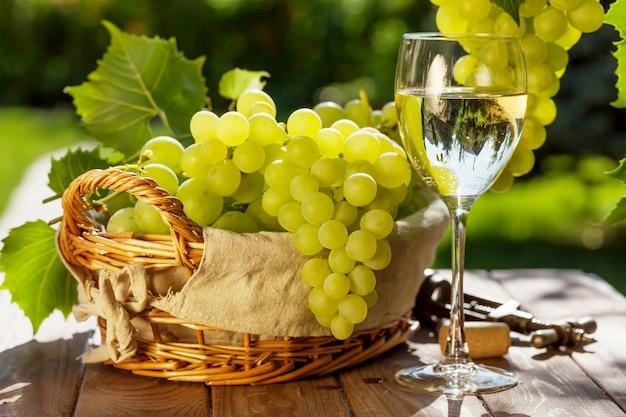 Copa de vino blanco, vid y racimo de uvas en la mesa de jardín