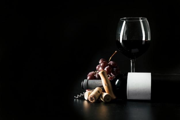 Copa de vino y botella cerca de sacacorchos y uva