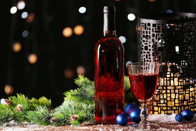Copa de vino y botella en mesa de madera decorada