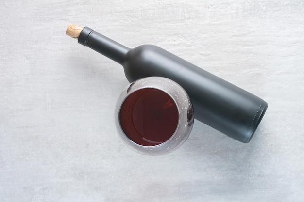 Una copa de vino con botella sobre superficie blanca