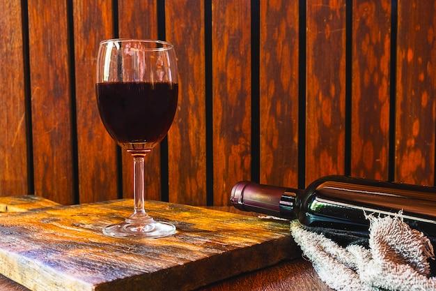 Copa de vino y botella de vino en la mesa de madera