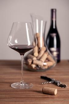 Copa de vino con botellas y corchos.