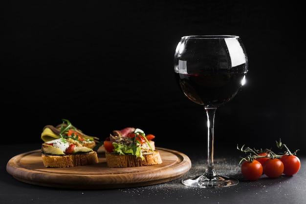 Copa de vino cerca de sándwiches abiertos