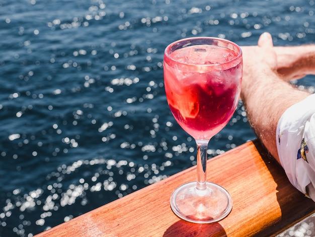 Copa de vino con cóctel rosa y cubitos de hielo.