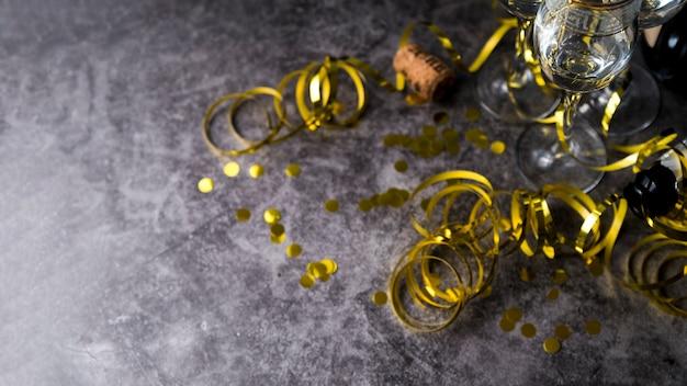 Copa de vino con confeti dorado decorativo y serpentinas sobre superficie de concreto