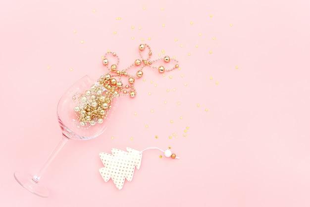 Copa de vino derramado decoración dorada, árbol de navidad y estrellas de confeti sobre fondo rosa. concepto de año nuevo y navidad