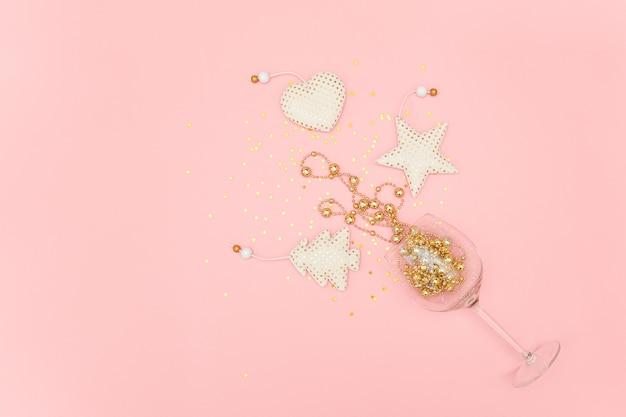 Copa de vino derramado decoración dorada de navidad y estrellas de confeti en rosa año nuevo, navidad, concepto de vacaciones