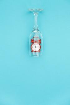 Copa de vino con despertador rojo dentro sobre fondo azul.