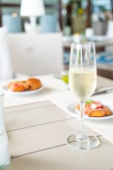 Copa de vino espumoso en la mesa en la cafetería restaurante