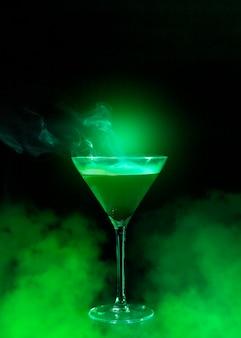 Copa de vino con licor y humo verde