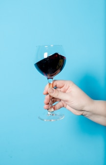 Una copa de vino en la mano de una mujer. fiesta de alcohol