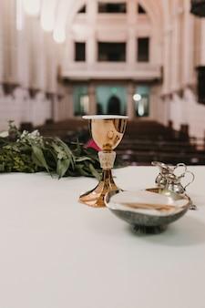Copa de vino en la mesa durante una ceremonia de boda misa nupcial. concepto de religión adornos eucarísticos católicos para la celebración de la eucaristía.