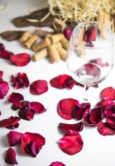 Copa de vino en la mesa con pétalos de rosa