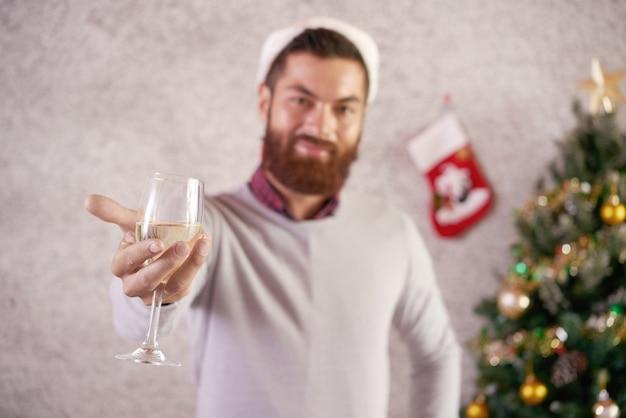 Copa de vino o champán en manos del invitado de la fiesta de navidad sonriente