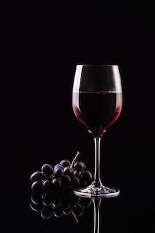 Una copa de vino en una pared negra con uvas. vino aromático estilo estricto. vino en la oscuridad