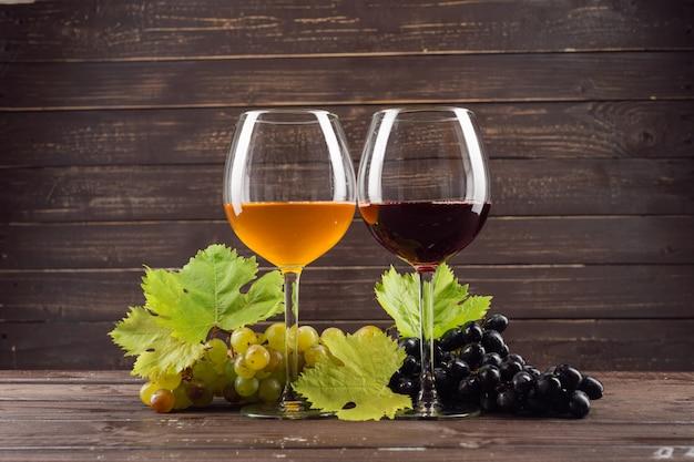 Copa de vino y racimo de uvas en mesa de madera