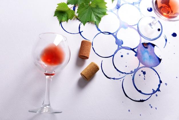 Copa de vino y rama de uvas pintadas con manchas de vidrio sobre papel blanco