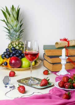 Copa de vino rosado en la mesa de madera blanca con libros antiguos y reloj, diferentes frutas tropicales y fresas