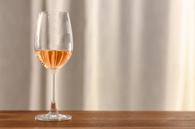La copa de vino rosado en mesa de madera.