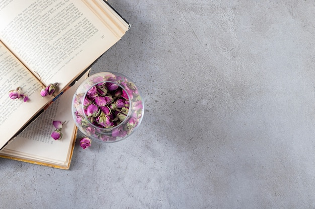 Copa de vino con rosas en ciernes y libros abiertos sobre fondo de piedra.