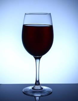 Una copa de vino sobre un fondo azul.