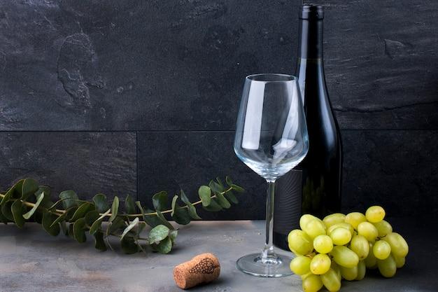 Una copa de vino sobre un fondo negro. uvas rosadas y verdes
