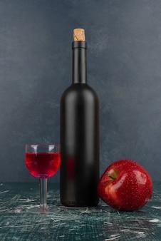 Copa de vino tinto y botella sobre mesa de mármol con manzana roja.