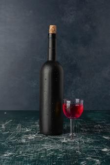 Copa de vino tinto y botella sobre mesa de mármol.