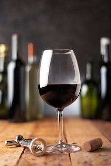 Copa de vino tinto con botellas detrás
