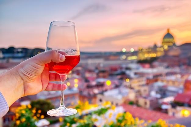 Copa de vino tinto contra la vista del paisaje urbano de roma con la catedral de san pedro.