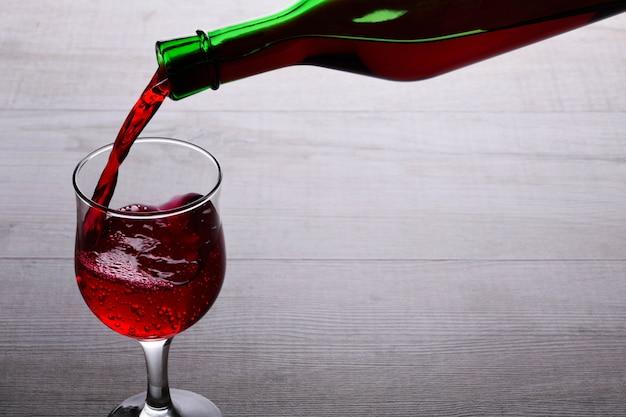 Copa de vino tinto. copa de vino sobre un fondo de madera clara