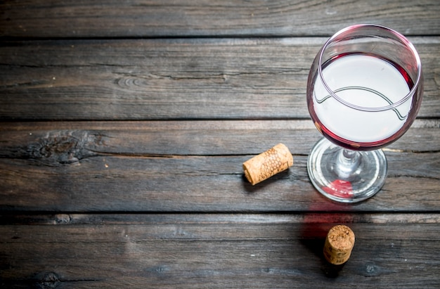 Una copa de vino tinto con corchos en una mesa de madera.