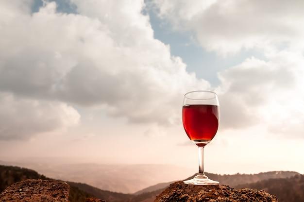 Copa de vino tinto y hermosa montaña de otoño Foto gratis