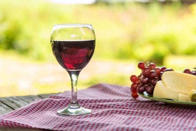 Una copa de vino tinto y un plato de queso, aceitunas y uvas sobre la mesa.