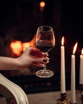 Una copa de vino tinto rodeado de velas en un ambiente romántico.