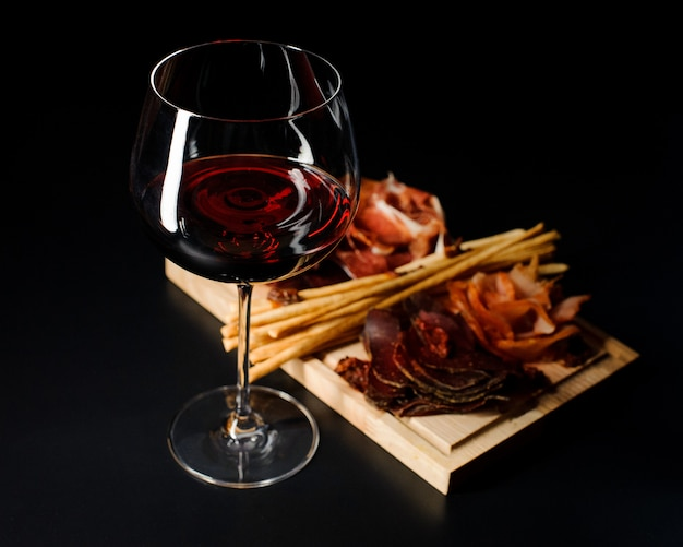 Copa de vino tinto seco y varios tipos de embutidos