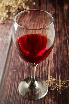 Copa de vino tinto sobre rústica, mesa de madera con textura.
