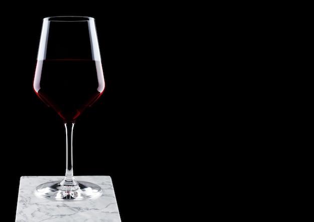 Copa de vino tinto sobre tablero de mármol blanco sobre fondo negro.