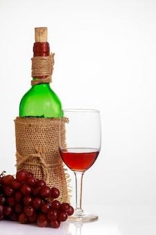 Copa de vino tinto con uvas y botella sobre fondo blanco.
