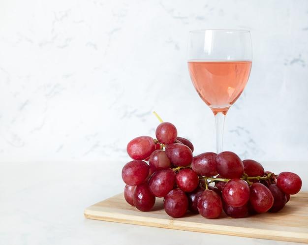 Copa de vino tinto y uvas sobre una tabla de madera.