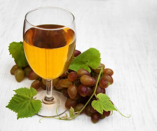 Copa con vino y uva blanca.