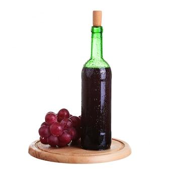 Copa de vino con vino tinto, botella de vino y uvas aisladas sobre fondo blanco.