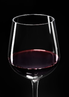 Copa de vino con vino tinto sobre fondo negro