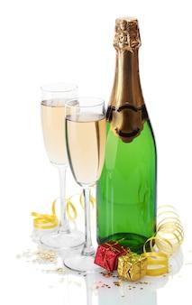 Copas y botella de champán, regalos y serpentina aislado en un blanco