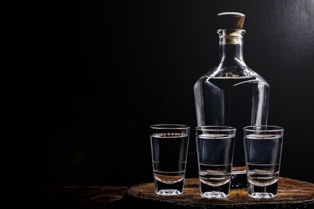 Copas de brandy con botella. botella sobre fondo negro con espacio de copia