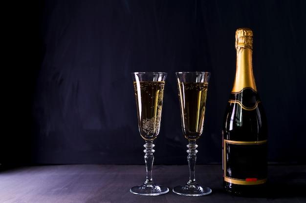 Copas de champagne con botella en la mesa